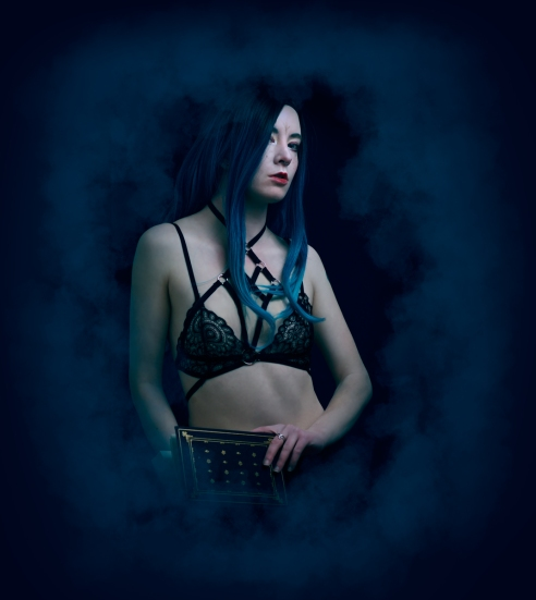 Dark, boudoir portrait featuring blue hair and black lace lingerie and a harness top.