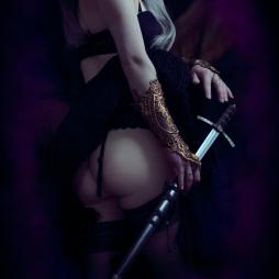 erotic fantasy boudoir portrait of a queen drawing her sword