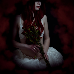Boudoir portrait of a red-haired angel holding flowers