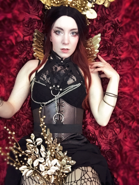 gold goth goddess in a floral headdress and chain harness holding gold flowers