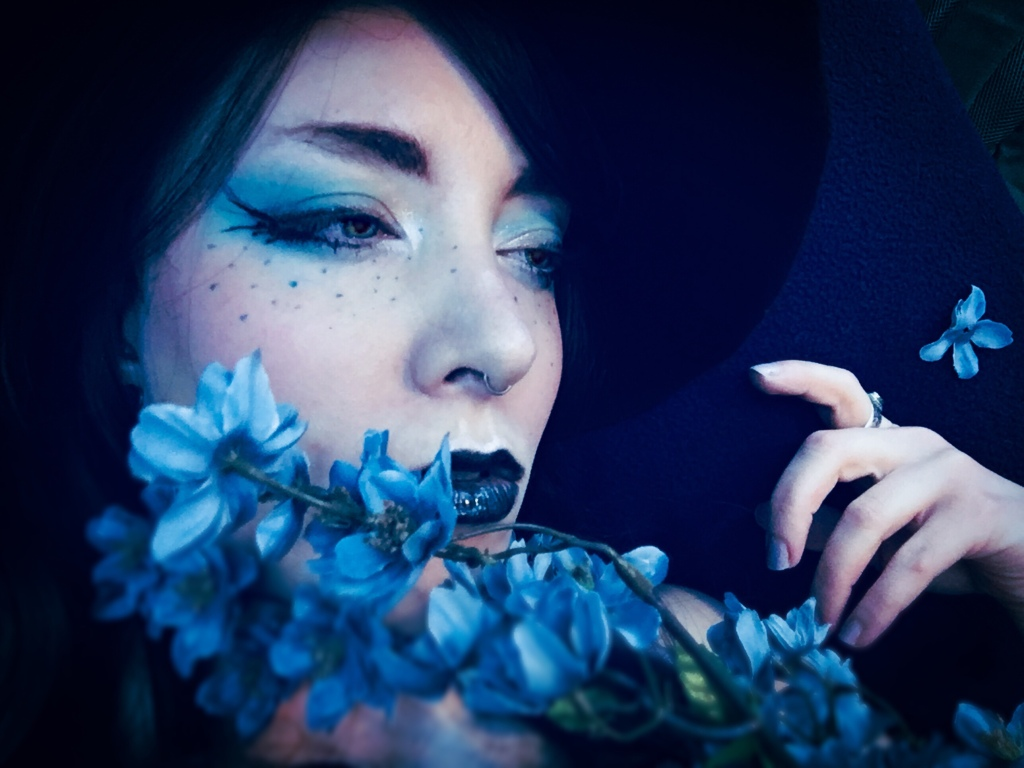 Beauty portrait of a femme with flowers and blue makeup