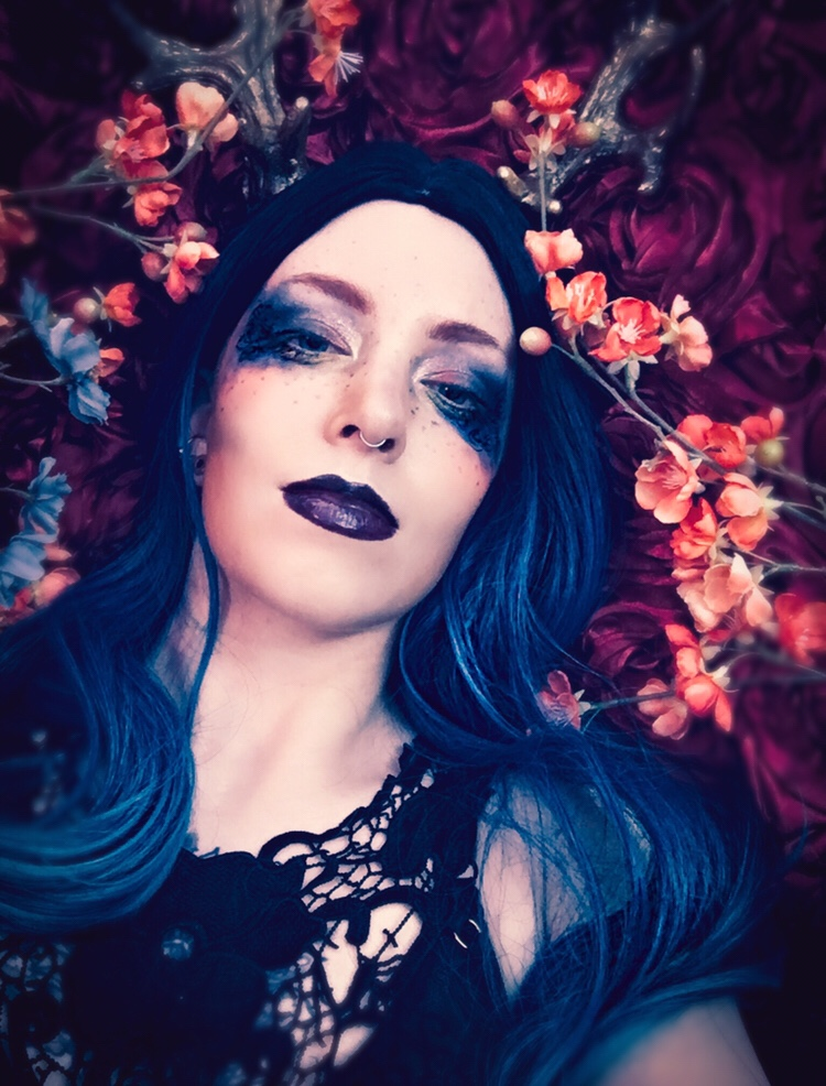 Floral glamour portrait of a genderqueer model with blue hair on a bed of flowers